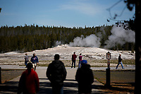 Tourists walk a boardwalk in front of Old Faithful in Yellowstone National Park, Wyoming on Tuesday, May 23, 2017. (Photo by James Brosher)