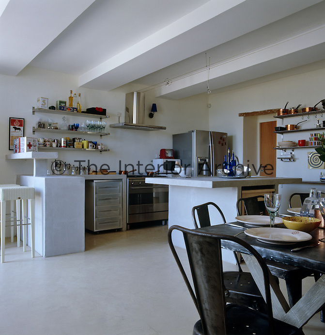 The industrial style open-plan kitchen has concrete units and stainless steel shelving