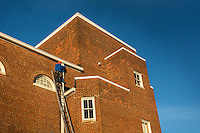 Worker install new rain gutters on the Masonic Hall on South State.