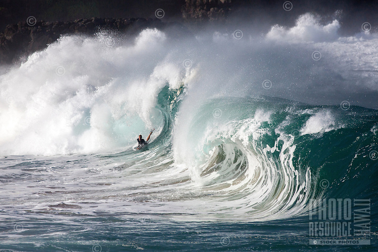 A bodyboarder rides a Waimea Shorebreak wave, North Shore, O'ahu.