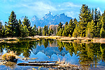 Clouds and mountains are reflected in the clear blue water in Grand Teton National Park in Wyoming.