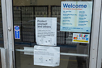 """A sign reading """"Protect yourself and others"""" and encourages 6 ft. social distancing for patrons of a United States Postal Service (USPS) branch in Belmont, Massachusetts, on Fri., March 20, 2020."""