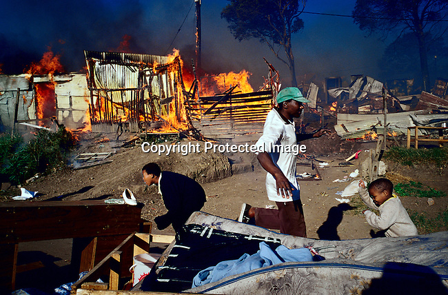 Residents rush to save their belongings as a shack fire is raging in Duncan Village, a poor township outside East London in Eastern Cape province, South Africa. It's on of the poorest areas in South Africa. Fires are very common as the shacks are built very close to each other and people are using paraffin stoves, which easily fall over, and the fires spread quickly. (Photo by: Per-Anders Pettersson)