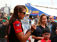Apr 26, 2014; Baytown, TX, USA; NHRA top fuel driver Leah Pritchett signing a hat for a fan during qualifying for the Spring Nationals at Royal Purple Raceway. Mandatory Credit: Mark J. Rebilas-