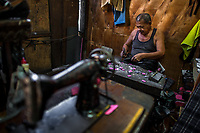 A Salvadoran shoemaker works with the shoe hammer, attaching a sole to a shoe, in a shoe making workshop in San Salvador, El Salvador, 16 November 2016.