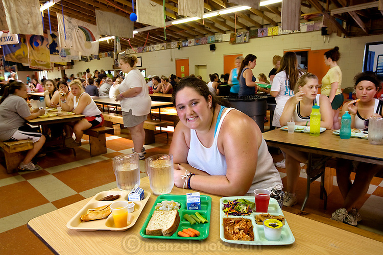 Mackenzie Wolfson with her prescribed day's worth of food in the cafeteria at Camp Shane weight loss cam in the Catskill Mountains, New York. (From the book What I Eat: Around the World in 80 Diets.) The caloric value of her typical day's worth of food in July was 1,700 kcals. She is 15 years of age; 5 feet, 9 inches tall; and 299 pounds. Dating back to 1968, Camp Shane is the oldest weight-loss camp in the country and is a heavy investment for parents. There are about 500 male and female campers housed in small cabins on shaded hillsides overlooking athletic fields, a small lake, and the camp's most important building, the cafeteria. ?The food here is not bad. It's not what I would order in a restaurant,? says 15-year-old Mackenzie. ?You know, its been prepared low-fat, low-sodium, but when you eat it you're like, whoa, this isn't that bad. And it's really good for me? But before everyone goes, they pig out the week before. One summer I probably gained about five pounds the week before I went to camp.? MODEL RELEASED.