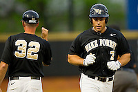 Mac Williamson #7 of the Wake Forest Demon Deacons gets a fist bump from head coach Tom Walter #32 as he rounds third base after hitting a solo home run against the Florida State Seminoles at Wake Forest Baseball Park on March 23, 2012 in Winston-Salem, North Carolina.  (Brian Westerholt/Four Seam Images)