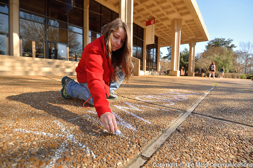 UM senior Sarah McCraw, a marketing assistant for the Department of Student Housing, draws with sidewalk chalk to promote Campus Walk Apartments, for which Student Housing is still accepting applications.  Photo by Nathan Latil/Ole Miss Communications