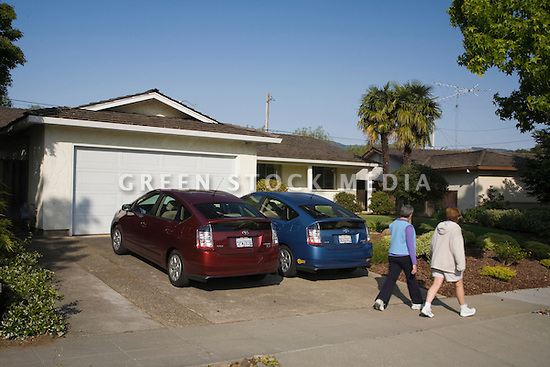 Two people passing two Toyota Prius hybrid cars which are parked in driveway. Cupertino, California, USA