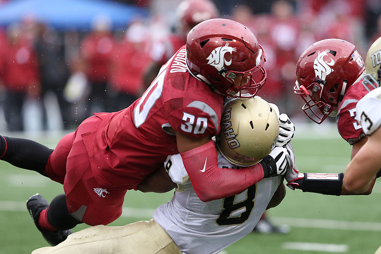 Nnamdi Oguayo, Washington State University defensive end, sacks the quarterback during the Cougars non-conference game against their neighbors from the University of Idaho on September 17, 2016.   The Cougs defeated the Vandals at Martin Stadium, 56-6.