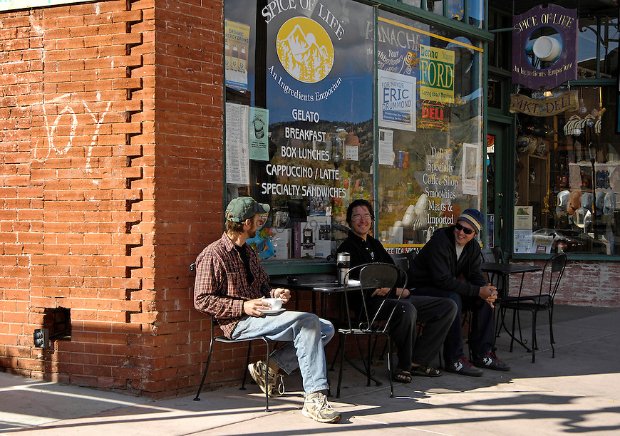 From the left, Andrew Appleseed, Doug Beechwood, and Cheyene Grow chat while Appleseed eats breakfast outside the Spice of Life Market and Deli. Michael Brands for The New York Times.