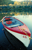 ROWBOAT AT REST ON PLACID LOON LAKE AT THE END OF FISHING SEASON.STILL, WATER, FALL, AUTUMN, BOAT. BRITISH COLUMBIA CANADA LOON LAKE.