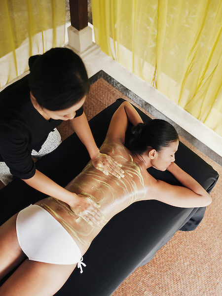 Woman receiving avocado body scrub at Rebab Spa, Kayumanis Gangsa, Bali, Indonesia. Avocado contains vitamins A, C, E and K, which helps a great deal to improve overall skin health and give a soft look and instant glow.