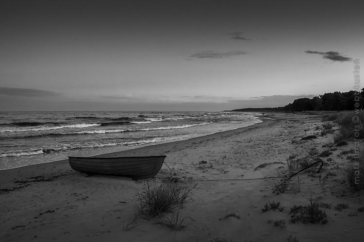 Båt på sandstrand i skymning över havet Östelen Skåne i svartvitt
