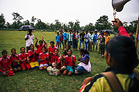 JAIPALGURI, INDIA- AUGUST 15: Player and coach of the female football team, the Dooars XI,  Bhabani Munda, 24, and players cheer on a fellow player as they receive a prize for coming second at a local derby on August 15, 2013 at the Kalchini tea estate In Jalpaiguri district , West Bengal, India. The Kalchini tea estate where Bhabani Munda lives is one of the most interior and backwards regions in north Bengal. The tea estates of North Bengal, including the Kalchini tea estate, were in news in 2007-08 for large-scale starvation deaths owing to malnutrition. Even today one person dies every day due to starvation in the north Bengal tea estates. In the last decade there have been 3500 deaths in these tea estates. (Photo by Daniel Berehulak for Time Magazine)