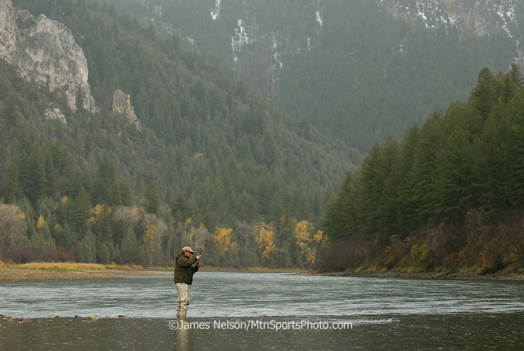 A fly fisherman plays a trout during a fall day in the canyon section of the South Fork of the Snake River, Idaho.