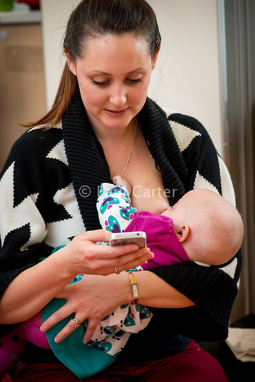 "A mother breastfeeds her baby while finding a picture on her mobile phone at a drop-in breastfeeding support centre.<br /> <br /> Image from the breastfeeding collection of the ""We Do It In Public"" documentary photography picture library project: <br />  www.breastfeedinginpublic.co.uk<br /> <br /> Hampshire, England, UK<br /> 13/03/2013<br /> <br /> © Paul Carter / wdiip.co.uk"