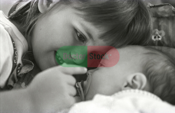 4 year old girl touching newborn girl's face