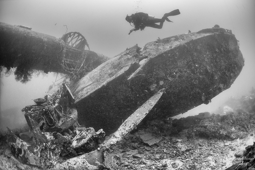 Tulagi, Florida Islands, Solomon Islands; a scuba diver swimming over the cockpit, viewed from below the right engine, wing and nose of a US PBY-5A Catalina seaplane, which was sunk during WWII, sitting upright on sand and rubble with it's wings intact but its engines having fallen from their mounts, laying next to the fuselage, just outside of Tulagi harbor