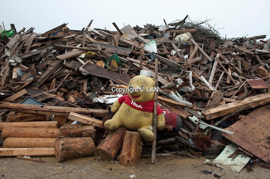 Landscape view of a stuffed animal and accumulated wood debris following the 311 Tohoku Tsunami in Tokura, Japan  © LAN