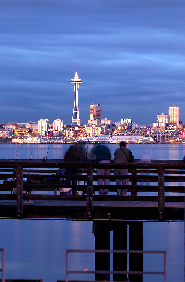 Fishermen on pier with Seattle skyline and Elliot Bay viewed from West Seattle, Seattle, Washington, USA