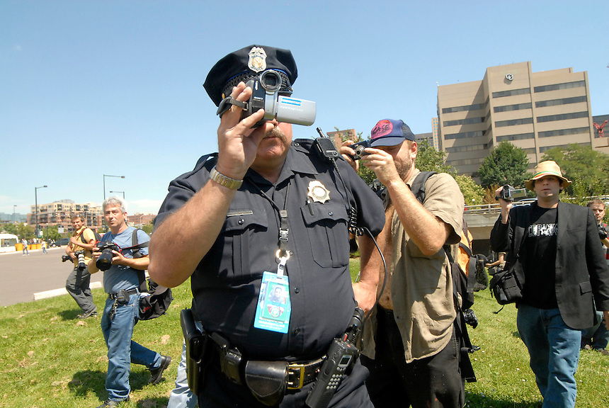 24 Aug 08: A police officer is photographed while pointing a video camera at protesters. On the day before the Democratic National Convention is scheduled to begin about 1,500 people participated in the ReCreate 68 rally, which included a march from the Colorado state capitol building to the Pepsi Center.