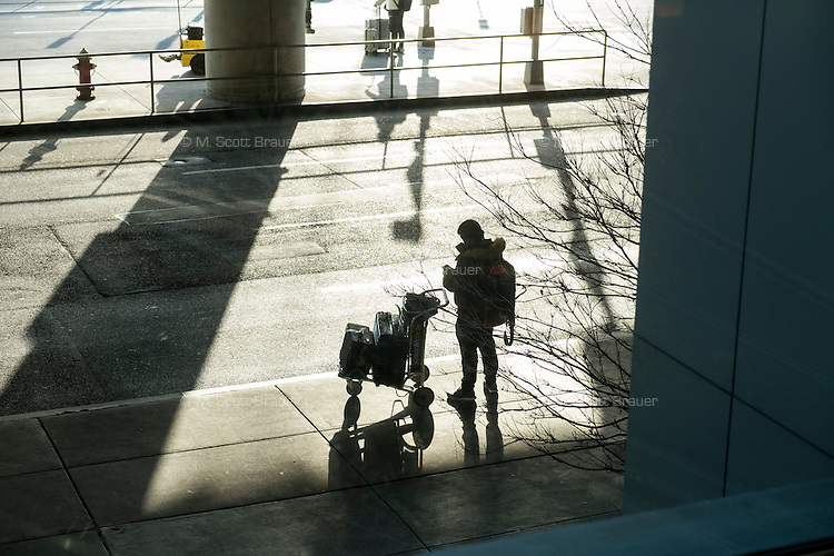 A man waits by the curbside outside Logan Airport Terminal E, the airport's international terminal, in Boston, Massachusetts, USA. An Executive Order signed by President Donald Trump bans travel for many from seven Muslim-majority countries.