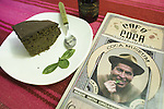 "The coca museum in La Paz, Bolivia.  Menu of the upstairs ""Coca Cafe"" and a slice of coca cake with a quintu of coca leaves on the plate."
