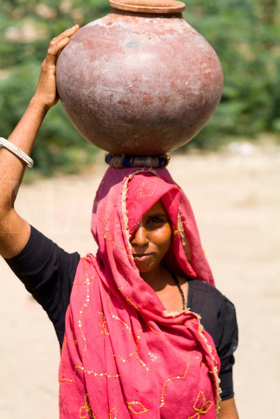 Local woman carrying water pot on head, small village of Chakhsu near Jaipur, Rajasthan, India