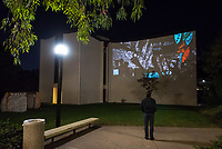 "Opening reception of the inaugural Ettinger Projected Poetry and Art Project: ""New"" World(s) which is a collaboration by Wanlass Artist in Residence Kenyatta A.C. Hinkle, media artist Keith Skretch, and ARTS290: Art Outside the Bounds students. The images and text are projected onto the south wall of Herrick Chapel and the reception was outside the Academic Commons, Dec. 7, 2017. Presented by Oxy Arts and CDLA.<br /> <br /> Students conducted research at Special Collections at Occidental College and amassed personal archives from prompts pertaining to personal narratives and images that haunted, challenged and provoked them. Students implemented interrupting the aesthetic of the didactic as a colonial tool of codifying. They also interviewed one another, and the residue of these questions and answers flicker in and out of the imagery. The context of the questions were formed by what roles we play within our family histories, how we absorb information as forms of truth and what does it mean to be an instrument of interruption, remixing, and restructuring narratives and historical and contemporary storytelling. Utilizing found imagery, objects and images from Herrick Chapel, these investigations weave in and out of one another, reminiscent of collage or a palimpsest of multiple interrogations and considerations of the truth.<br /> The Ettinger Projected Poetry and Art Project is a public art project that infuses the written word and images into everyday moments around campus. Presented nightly for several hours during reading days and finals week each semester through spring 2020, the rotating exhibitions will project provocative and intellectual work on frequently viewed spaces on campus, inspiring deep collaborations between the arts and digital sciences and building pathways and partnerships that mirror our increasingly pluralistic world.<br /> The Wanlass Artist in Residence is Occidental's annual residency program that allows an artist to investigate aspects of their practice and"