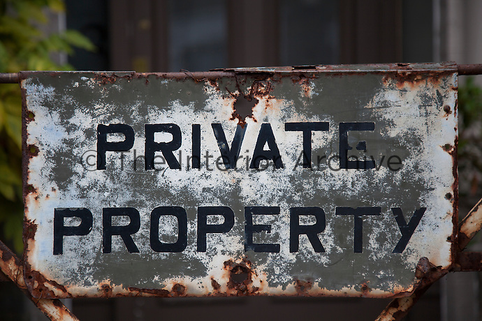 Close-up of the rusting metal sign hung on the entrance gate