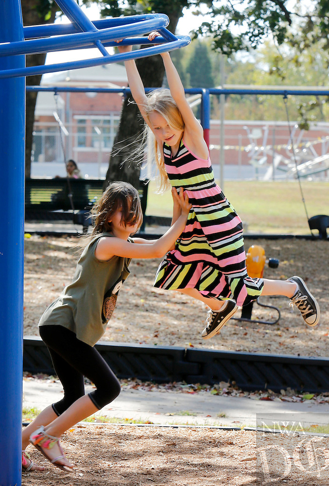 NWA Democrat-Gazette/DAVID GOTTSCHALK  Cheyene (cq) Helems, 10, gives Laurin Jacobs, 8, a push Monday, October 17, 2016, to propel her around a hanging carousel at Creekmore Park in Fort Smith. The two girls where with family enjoying the nice the weather.