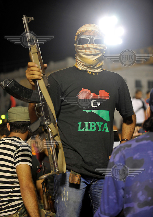 A masked rebel holds a gun and wears a t-shirt with the national flag on it as he celebrates at Martyrs' Square in Tripoli. After a six month revolution, rebel forces finally managed to break into Tripoli and have taken control of Bab al-Aziziyah, Col Gaddafi's compound and residence. Few remain that are loyal to Gaddafi in the city; it is seeming that the 42 year regime has come to an end. Gaddafi is currently on the run.