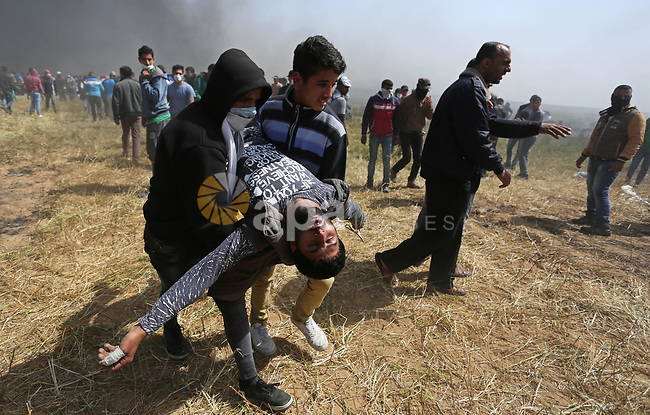 A wounded Palestinian protester is evacuated during clashes with Israeli security forces at the Israel-Gaza border in a tent city protest demanding the right to return to their homeland, in Khan Younis in the southern Gaza strip on April 6, 2018. Photo by Ashraf Amra