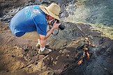 GALAPAGOS ISLANDS, ECUADOR, Tangus Cove, a man photographing sally lightfoot crabs on the rocks near the water on the NW side of Isabela Island