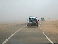 Merzouga, Morocco.  Wind Blows Sand Across the Road as vehicles Leave Merzouga.