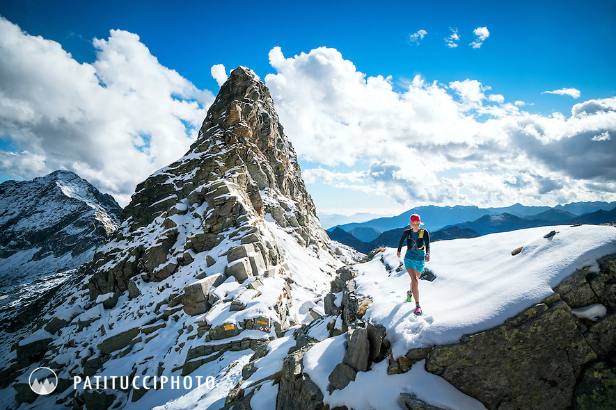 A woman trail running from Val Verzasca in snow on the trail to Monte Zucchero, a 2735 meter summit in the Ticino region of Switzerland.