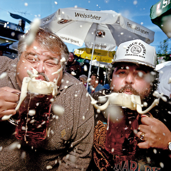 Two men blow foam from the tops of the their big steins
