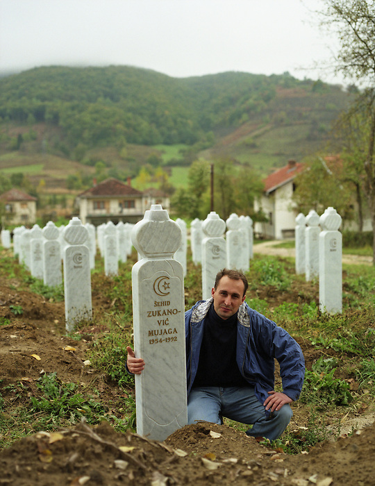 1997.A young man kneels with his arm around the grave of his brother, murdered by Chetniks in 'ethnic cleansing' in Bosnia in 1992...Biljani-Sanica, NorthWest Bosnia, 1997.