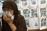 Sahamiah Jehteh recoils from a bulletin board showing pictures of the dead that were found following the Asian Tsunami. Bulletin boards like this one in Bang Niang, Thailand line the roads in coastal areas. Officials hope that the pictures of the dead, though sometimes badly disfigured, may allow for family members to identify their missing relatives. January 7, 2005. (James J. Lee for USA Today)