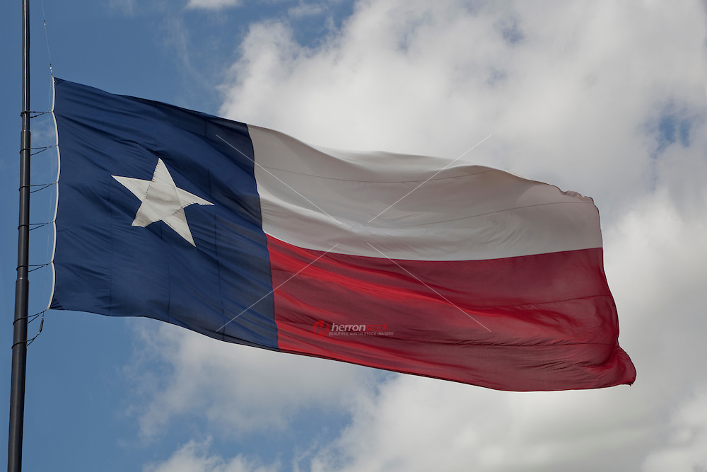 The mightily State of Texas Flag flys Against a cloudy blue Sky
