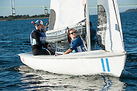 Salve's Jen Killian,'17, left, captain, and Madeline Lark,'19, crew, work together in the Newport Harbor as they practice with other members of the Salve Regina Sailing Team.