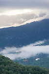 The clouds in the mountains of Corsica reveal a white building nestled amongst the trees.
