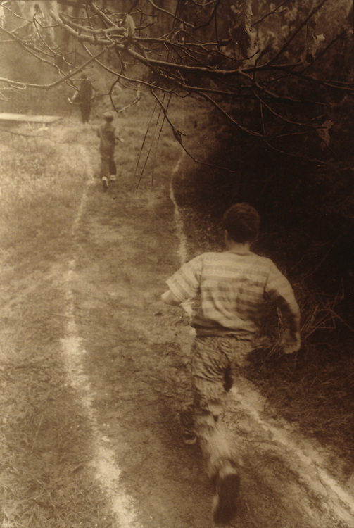 boys running on path in woods