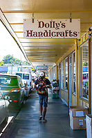 A young man with a backpack walks under the sign for Dolly's Handicrafts on Mamo Street in downtown Hilo, Big Island of Hawai'i.