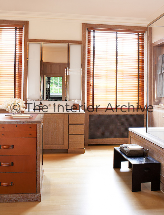 In this large bespoke bathroom the central island offers storage space wth a series of leather covered drawers