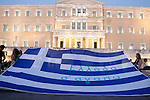 Anti-austerity protesters with Greek flag outside the Greek parliament. Greece's prime minister was fighting to keep his government intact in the face of outrage over an austerity bill that parliament must pass Wednesday night if the country is to start negotiations on a new bailout and avoid financial collapse. The raft of consumer tax increases and pension reforms will condemn Greeks to years of more economic hardship and has fueled anger among the governing left-wing Syriza party.