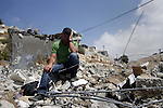The brother of Shaker Ja'abis sits on the rubble of his brother's home after demolishing it by bulldozer in Jabel Mukaber neighborhood southern Jerusalem on Sep 05, 2013. Ja'abis decided to demolish his own home to carry out an Israeli court order under the pretext of building without municipality permit. Many Palestinians end up demolishing their homes themselves to avoid the high cost of paying for Israeli government bulldozers, or being sent to prison for not being able to pay. Photo by Saeed Qaq