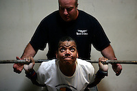 09162009 - Paula Houston, Powerlifter, SU grad student..Paula Houston (cq) 48, a graduate student at Seattle University and the executive director of the Meredith Mathews East Madison YMCA pushes upward out of the bottom of a squat position as her trainer Todd Christensen (cq) owner of the powerlifting/strongman gym Seattle Strength and Power spots her during a lifting session Sept. 16, 2009.  Houston is a world champion powerlifter and has been powerlifting for close to 25 years.