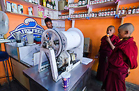 Young Buddhist monks wearing red robes, buying ice cream at shop in Leh, Ladakh, India.